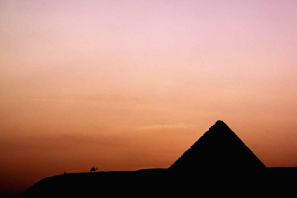 Silhouette of camel rider approaching Menkaure Pyramid at sunset. This is the smallest of the 3 Giza pyramids. W0384b