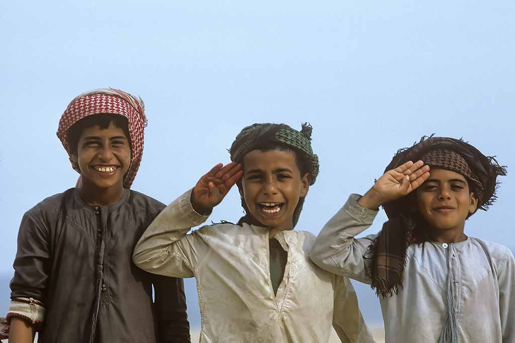 Bedouin boys happily posing for the camera in the Wahiba desert of Oman. W10671