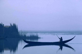 Dream-like image of a woman silently punting her slender canoe pre-dawn in the Central Marshes. W8881
