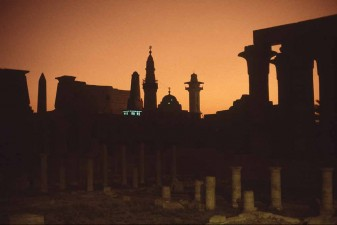 Luxor Temple and silhouetted mosques and minarets. Lights are from a minaret. W0829