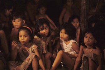 Dayak children in the faint light of open fire in longhouse in Sarawak, Borneo. Theu are descendants of the head hunters. Malaysia. W10059