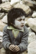 Mexico. Tarahumara Indian boy painted with ashes for Easter celebrations. He is suffering from early morning cold. W10140
