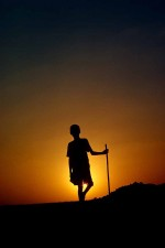 Young Sudanese boy in classical standing and resting position silhouetted against a gloriouis sunset. This in an area called Rahad. W10601
