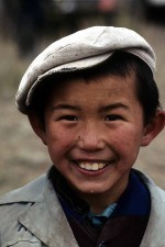 A happy young Kazakh boy with a great smile. He is watching horse racing, a favorite sport in Kazakhstan, Western China. W11245