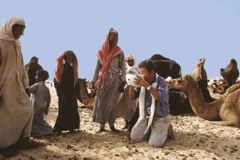 Tor Eigeland drowns his thirst in a fresh bowl of frothy camel's milk to the amusement of Al-Murrah Bedouin. W6073